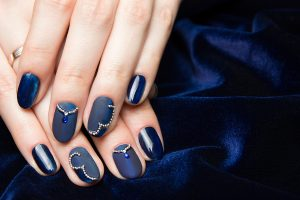 Beautiful manicured female hands with French manicure on dark blue background