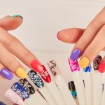 Manicured hands and polish color samples. Manicured hands touching nail sample with different design. Artificial nails on transparent basis. Varnish color palette for nails.